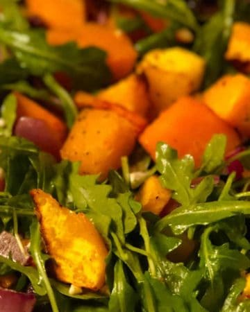 a closeup of roasted butternut squash salad over arugula