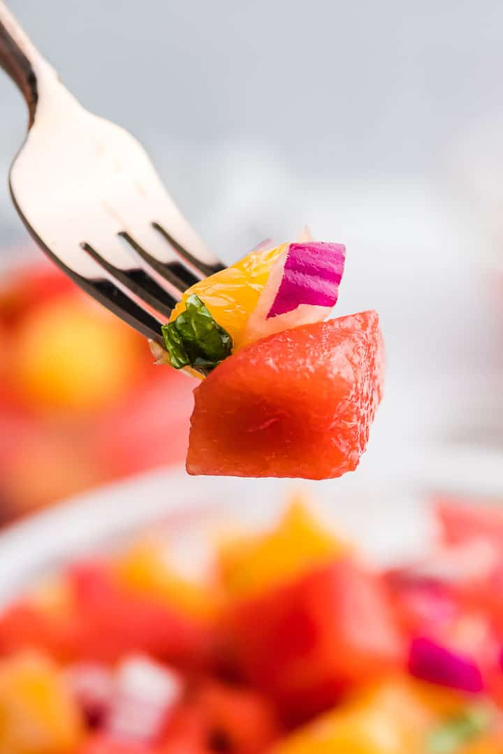 a forkful of watermelon and orange salad