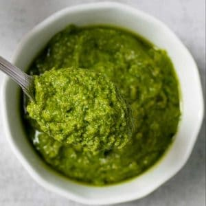 A spoonful of parsley pesto served from a white bowl