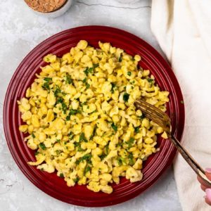A plate of homemade spaetzle cooked in butter and drizzled with parsley