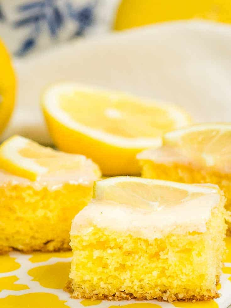 Slices of baked lemon pound cake topped with a thin slice of lemon
