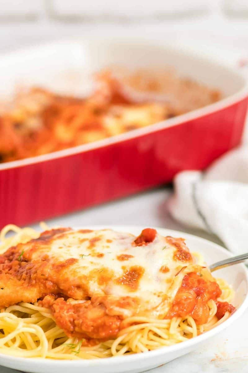 a white place with spaghetti pasta and topped with deliciously cheesy chicken parmesan