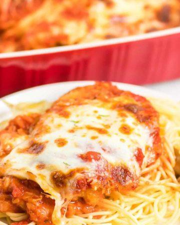 freshly baked chicken served over spaghetti pasta
