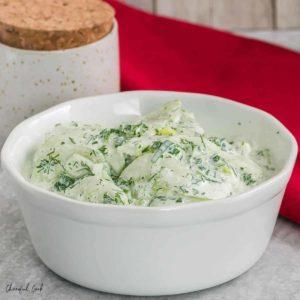 a bowl of creamy cucumber salad in a fresh herb dressing
