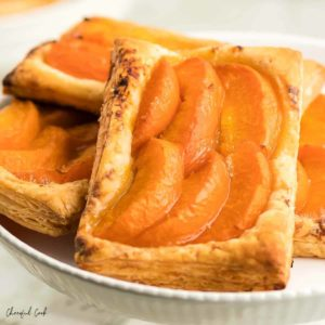 4 apricot tarts on a white cake stand