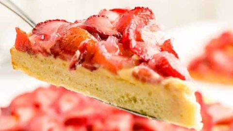 a slice of freshly bake Erdbeerkuchen (German Strawberry Torte) with a side of whipped cream