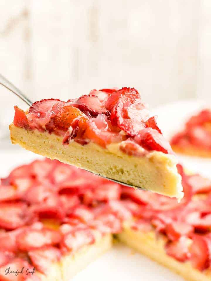 a slice of freshly sliced German strawberry cake, straight from a white cakestand