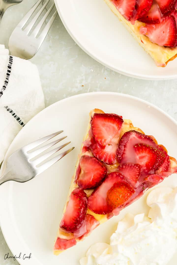 a slice of Strawberry Torte with a side of whipped cream on a white plate