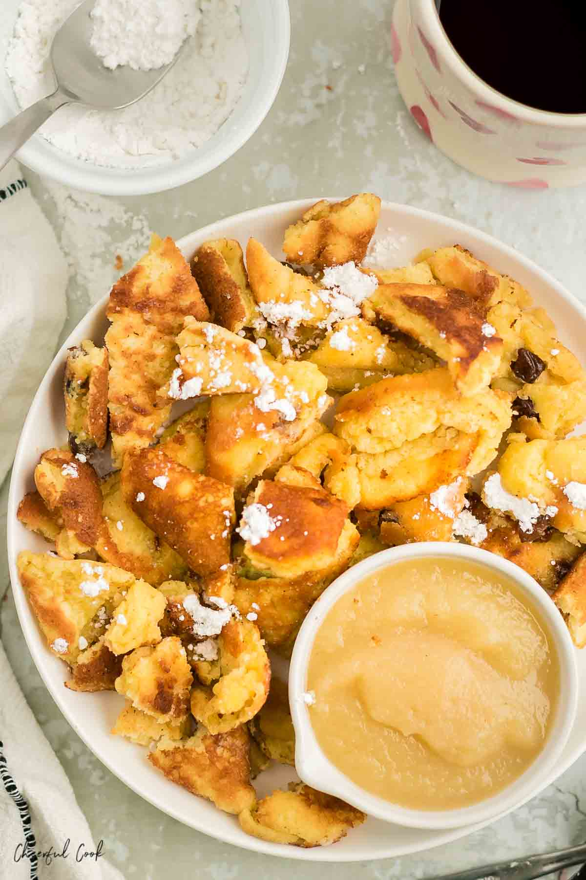 kaiserschmarrn on a white plate with applesauce and a white bowl of powdered sugar