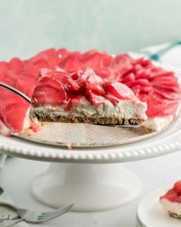 A slice of no bake strawberry cheesecake taken off a white cake stand