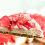A closeup of a slice of no bake strawberry cheesecake