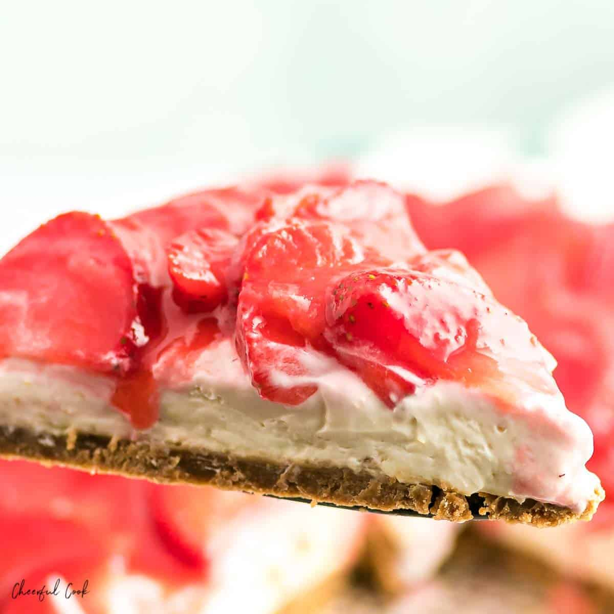 A closeup of a slice of no bake strawberry cheesecake