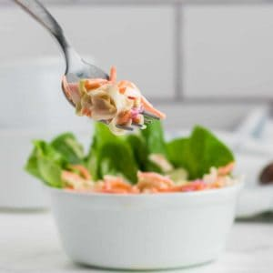 a forkful of creamy cole slaw out of a white bowl