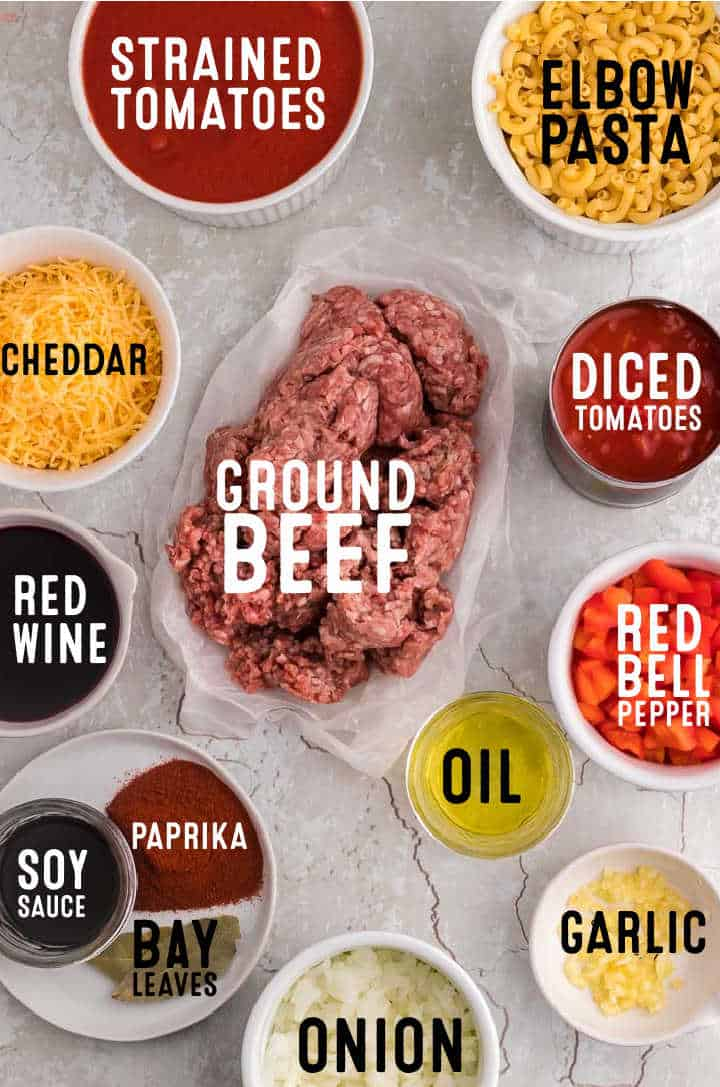 Ingredients needed to make Ground Beef Goulash (American Goulash): strained tomatoes, elbow pasta, cheddar, ground beef, diced tomatoes, red wine, soy sauce, paprika, red bell peppers, bay leaves, onions, oil, and garlic