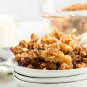 freshly baked apple crisp served on a white place with vanilla ice cream