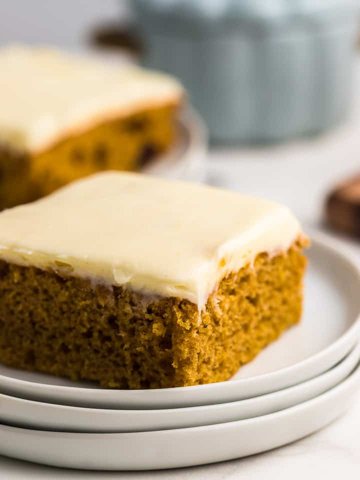 a slice of freshly baked pumpkin sheet cake on a white plate