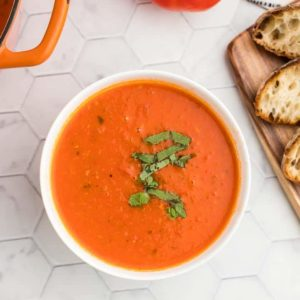 a bowl of fresh tomato soup topped with fresh basil