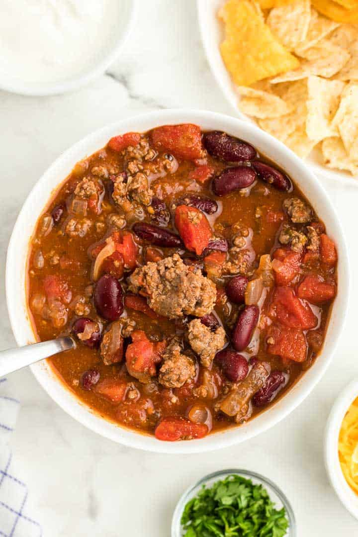 a white bowl of freshly cooked chili with a spoon