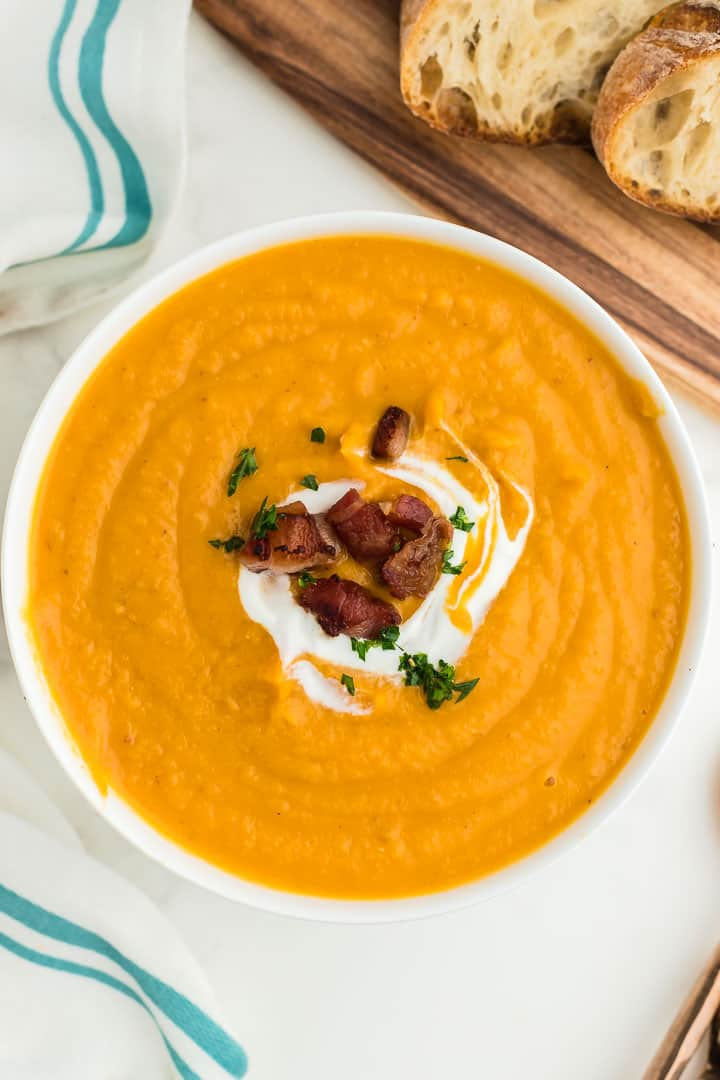 a large bowl of creamy sweet potato soup topped with a swirl of sour cream and drizzled with bacon