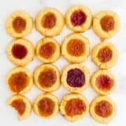16 freshly baked Thumbprint Cookies (German Engelsaugen) with one cheeky bite taken out of one cookie