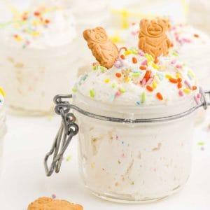 mason jar full of dunkaroo dip topped with two graham cracker animal cookies