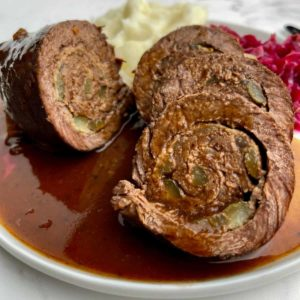 sliced freshly cooked German rouladen on a white plate with mashed potatoes and red cabbage