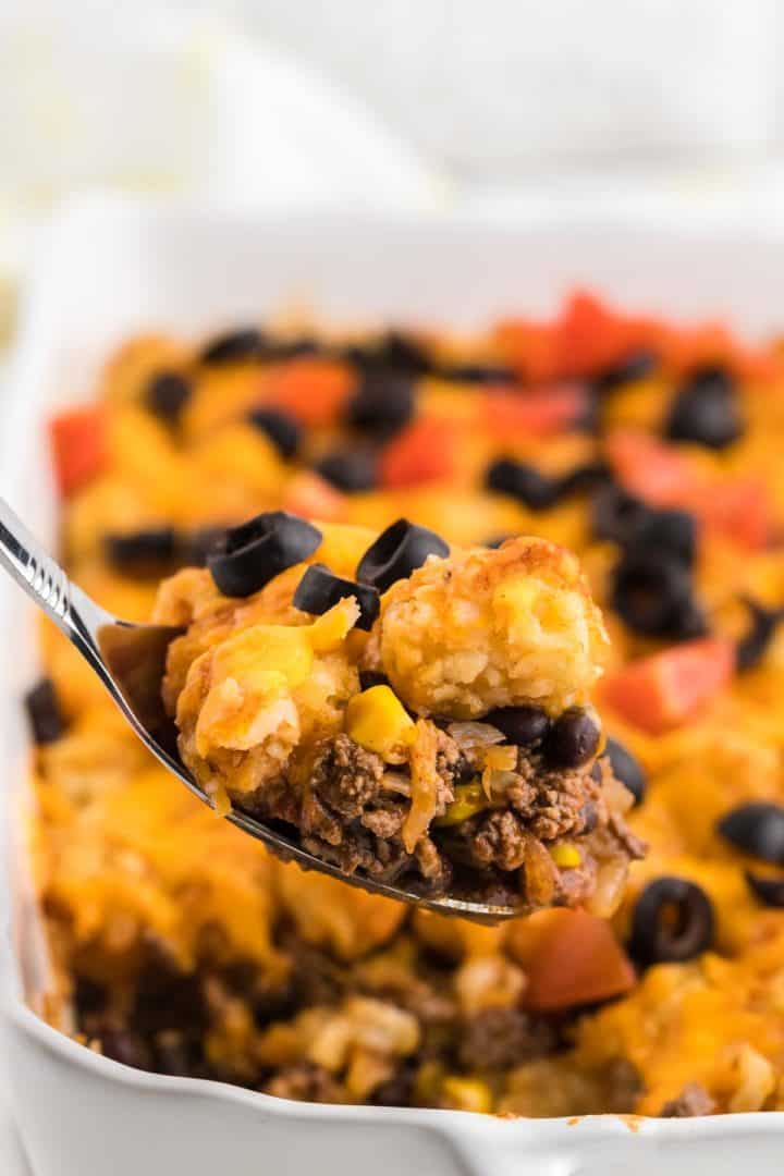 a spoonful of freshly baked taco tater tot casserole straight out of the baking dish
