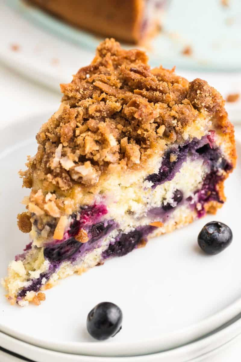 a slice of freshly baked Blueberry Coffee Cake on a white cake