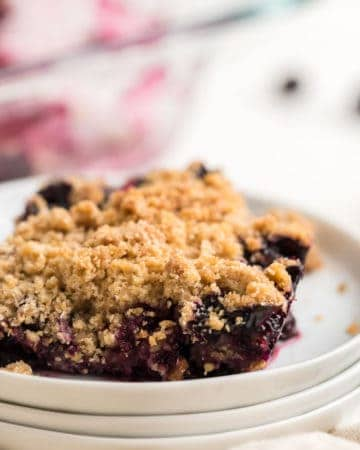 a slice of blueberry crisp on a white place