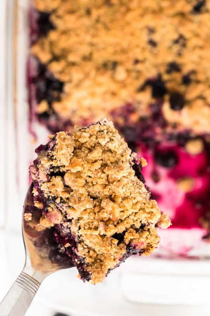 a slice of freshly baked blueberry crisp on a serving spoon