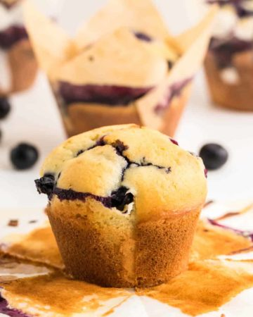 a closeup image of a freshly baked blueberry muffin with the liner removed