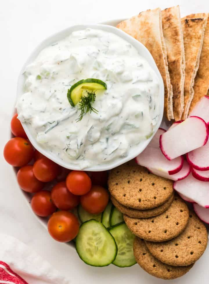 cucumber dip in a bowl served on a platter of fresh veggies, crackers, and pita bread