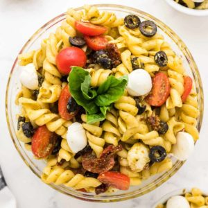 freshly made pesto pasta salad in a glass serving bowl