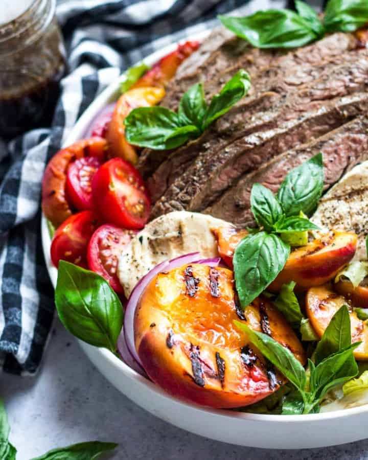 Grilled Flank Steak Salad with Peaches in a white bowl | boulderlocavore.com