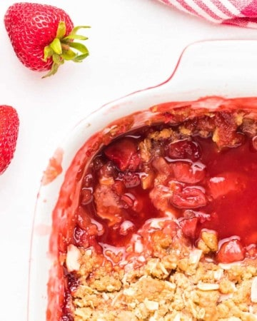 strawberry crumble in white baking dish with two sliced removed