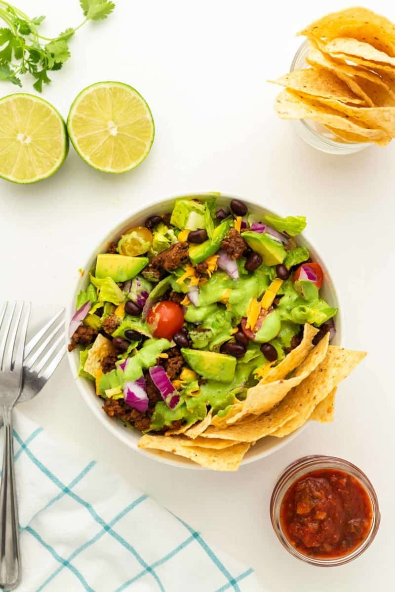 Ground Beef Taco Salad in white bowl topped with Cilantro Lime Dressing