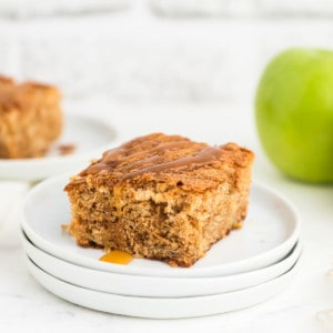 a slice of freshly baked apple cake drizzled with caramel sauce