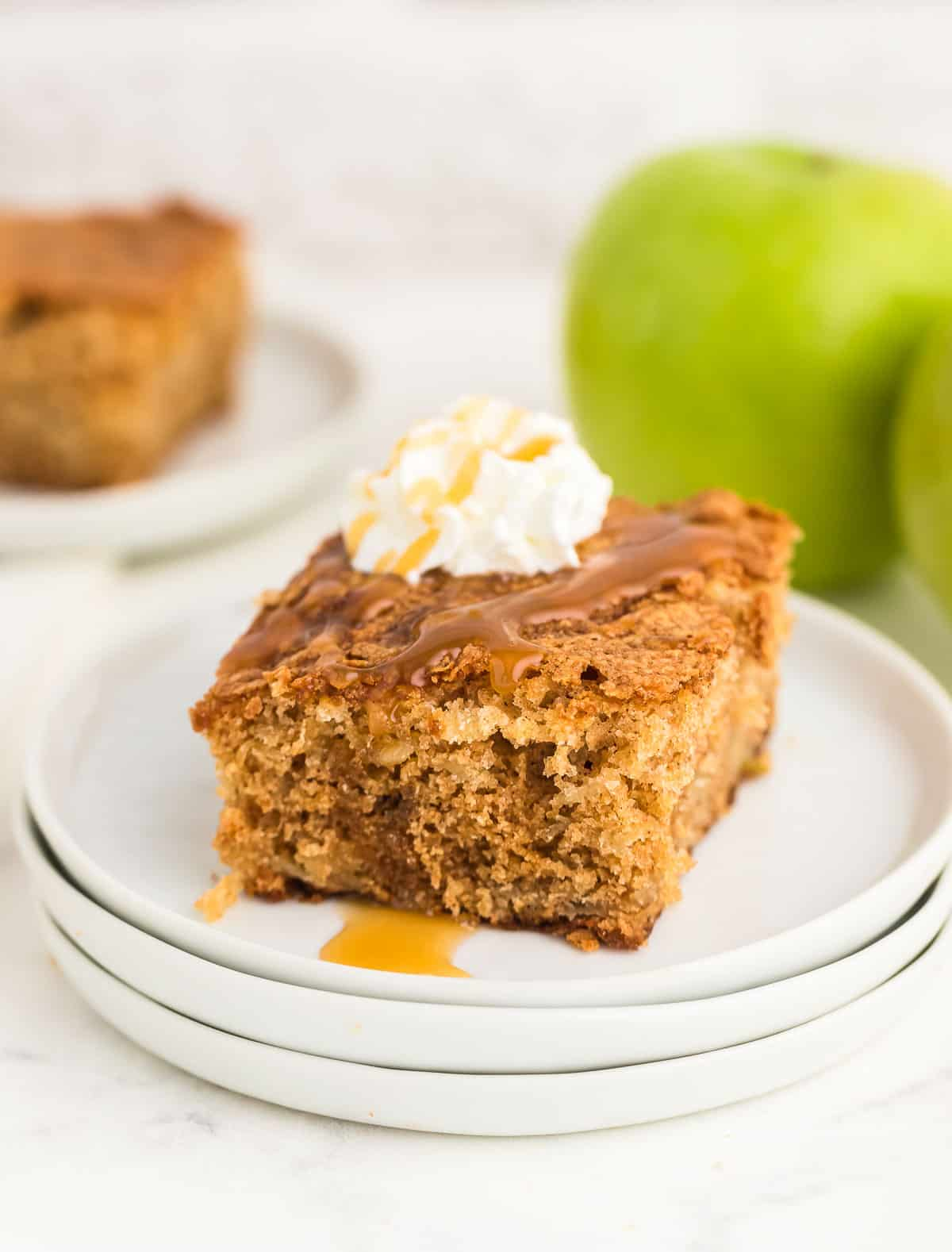 a slice of Apple Cake with cream and caramel sauce