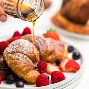 drizzling maple syrup over the croissant french toast
