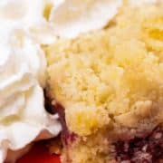 A slice of Cherry Crumble with a blob of whipped cream