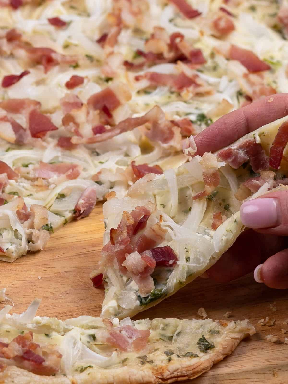Taking a slice of freshly baked Flammkuchen