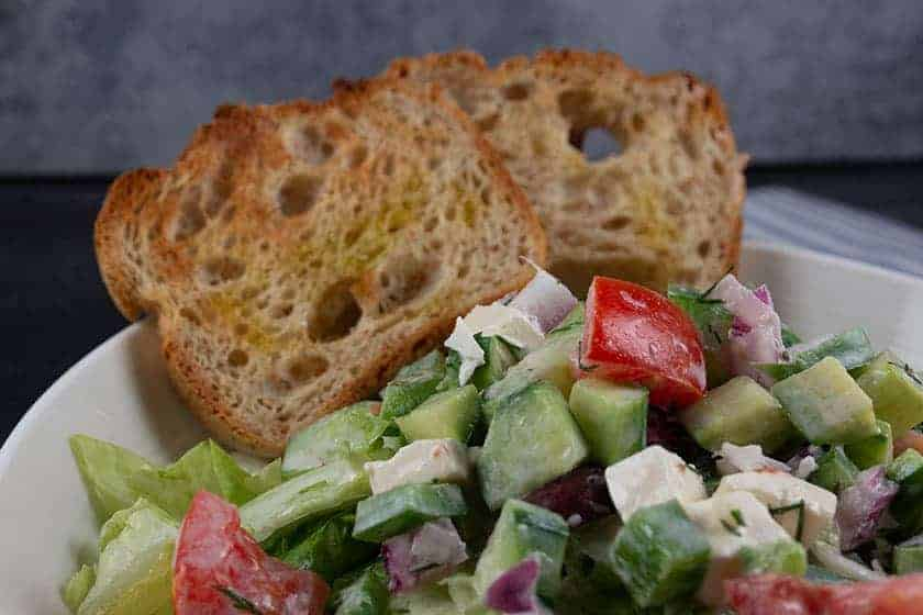 Salad bowl with Greek Salad and two slices of toasted gluten free bread