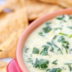 A bowl of warm Spinach Dip with Nachos chips for dipping
