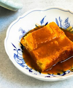 A plate of warm custard bread pudding with homemade caramel sauce
