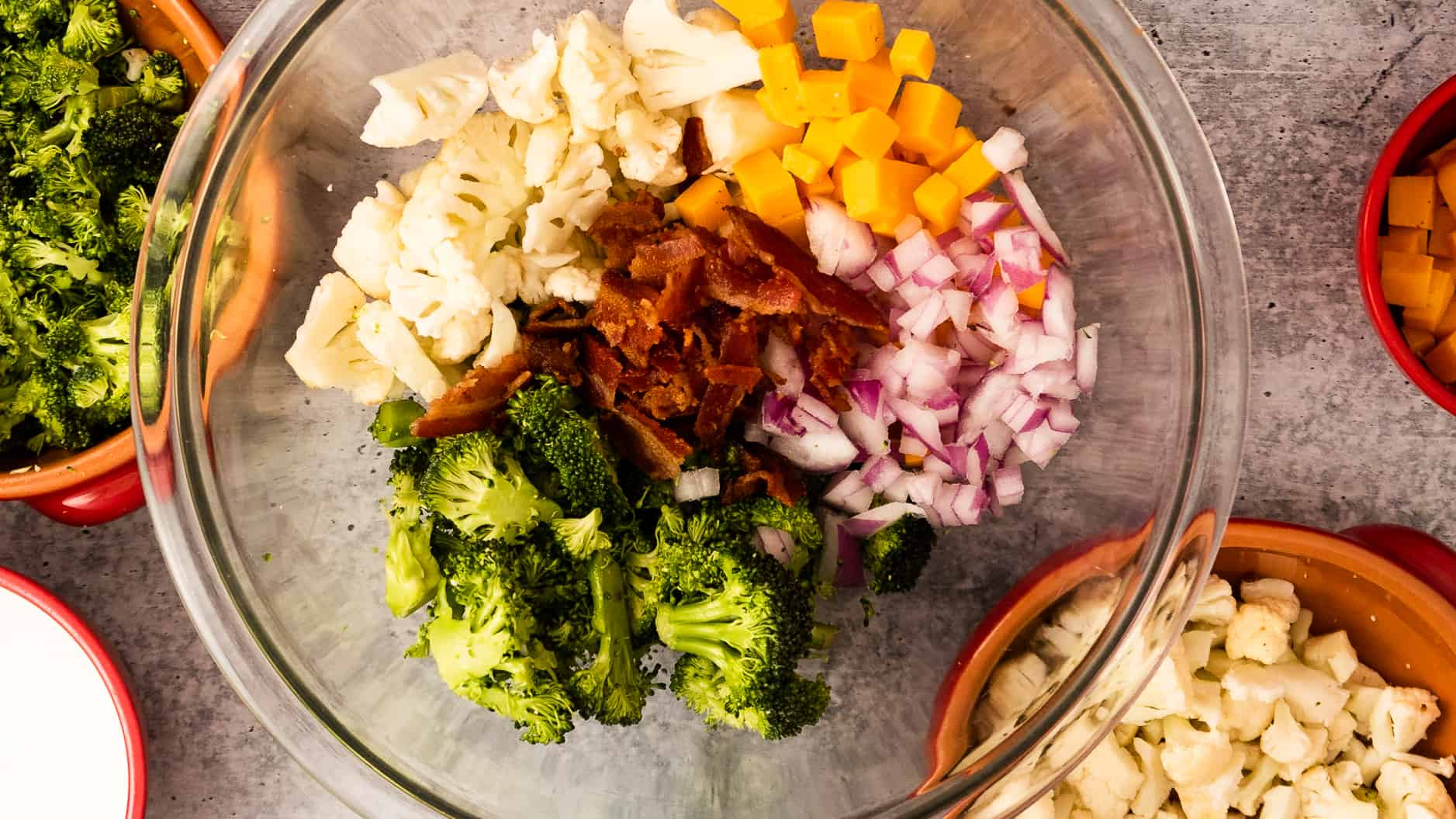 A bowl of broccoli, cauliflower, bacon, red onion, and Cheddar cheese!