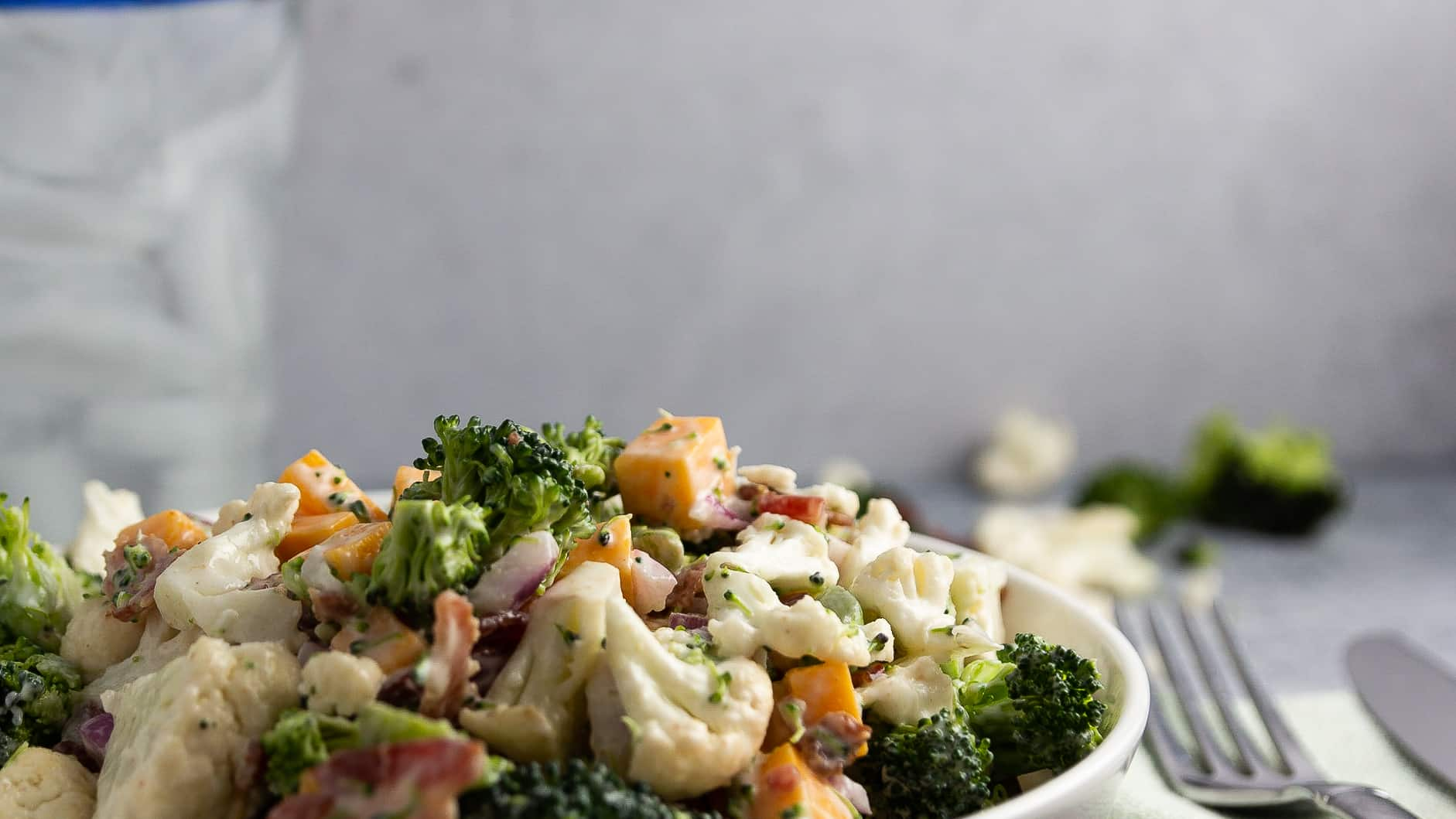 A bowl of cold broccoli cauliflower salad.