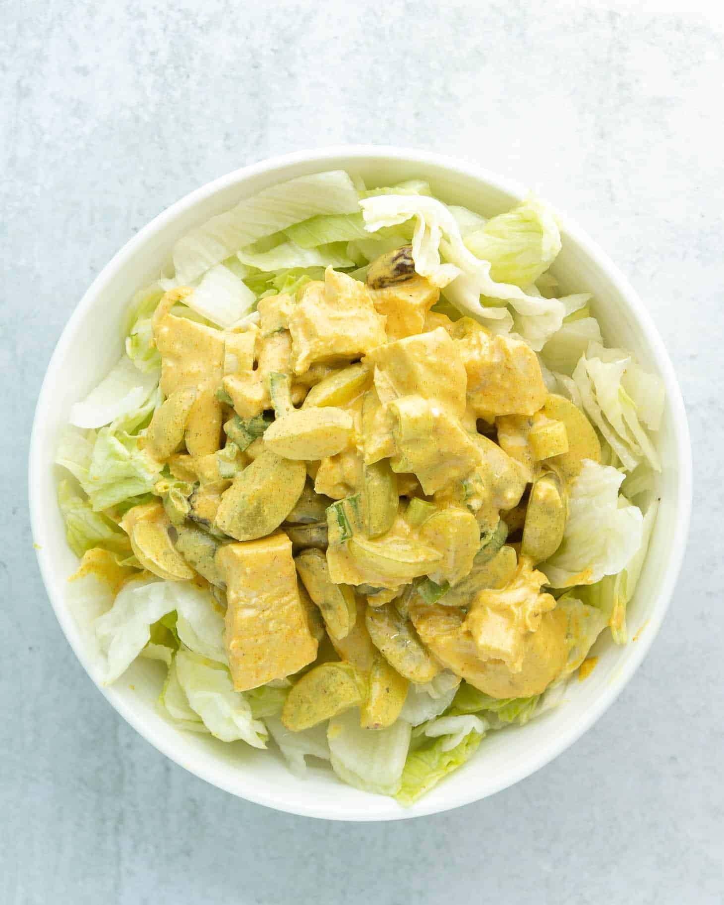 A bowl of curry chicken salad with grapes