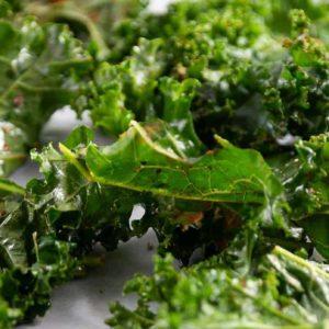 seasoned kale spread on a baking sheet ready for roasting