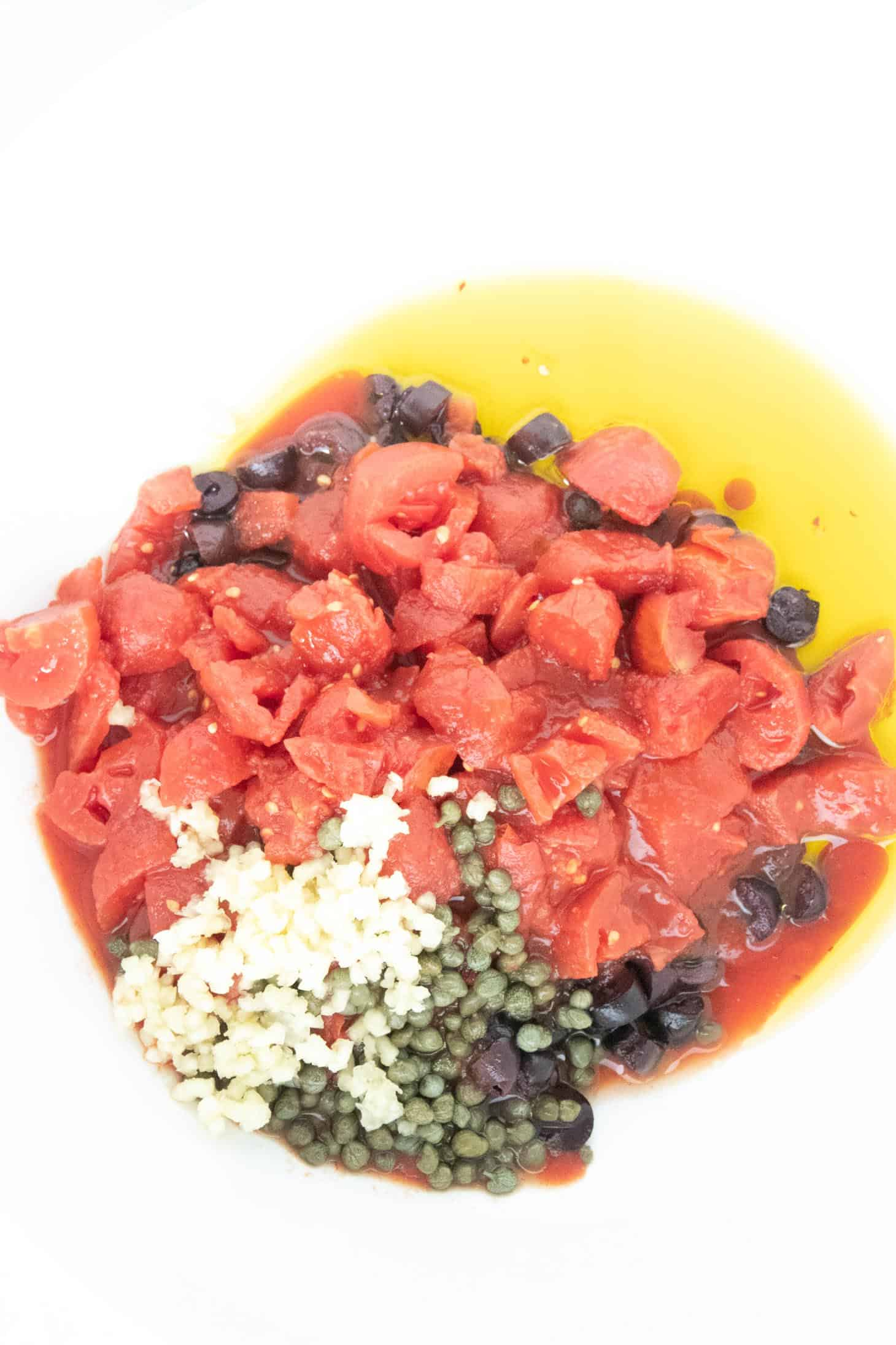 A bowl with olive oil, garlic, diced tomatoes, capers, olives