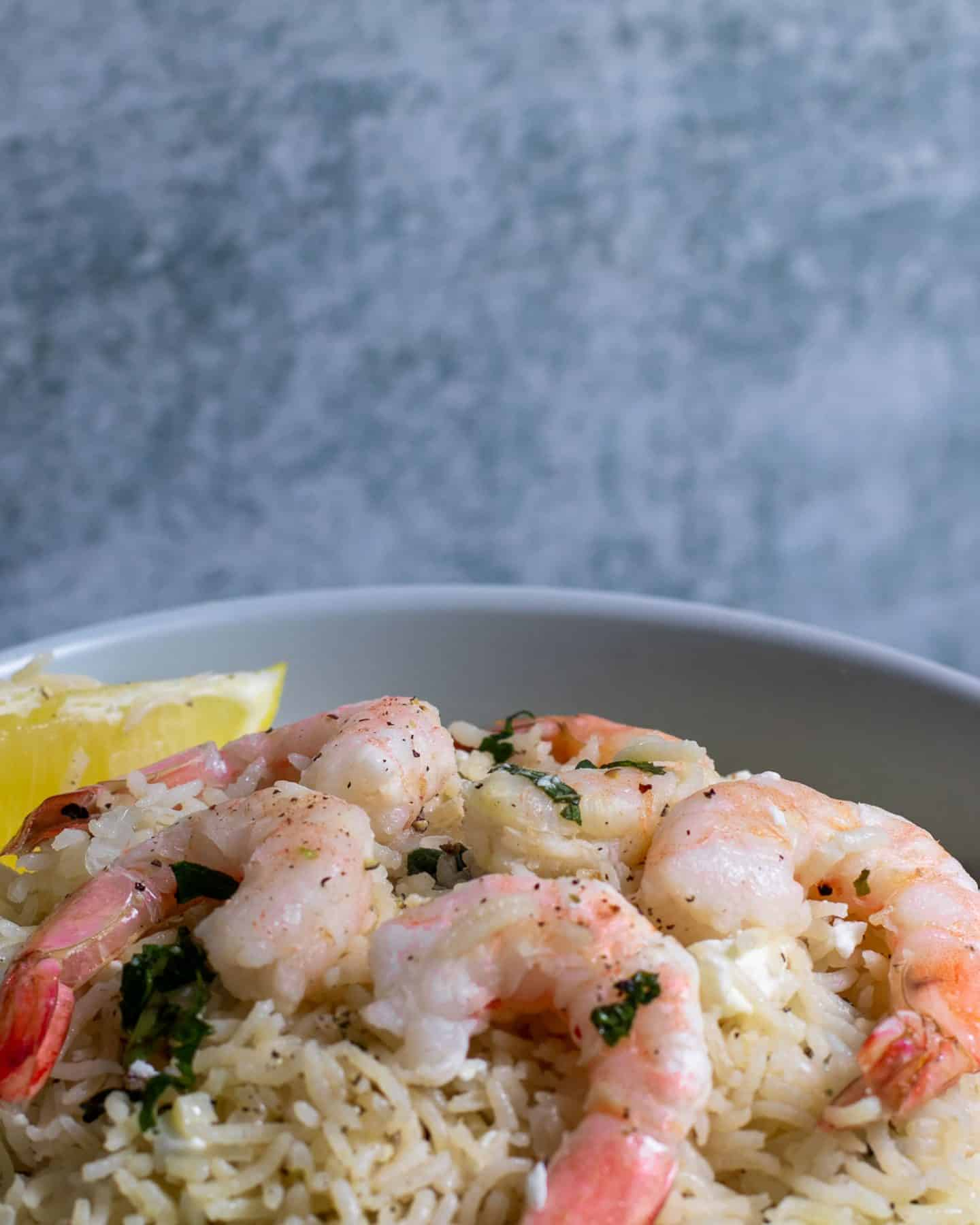Mint Rice with shrimp and a wedge of lemon.